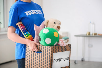 Female volunteer holding donation box with toys indoors
